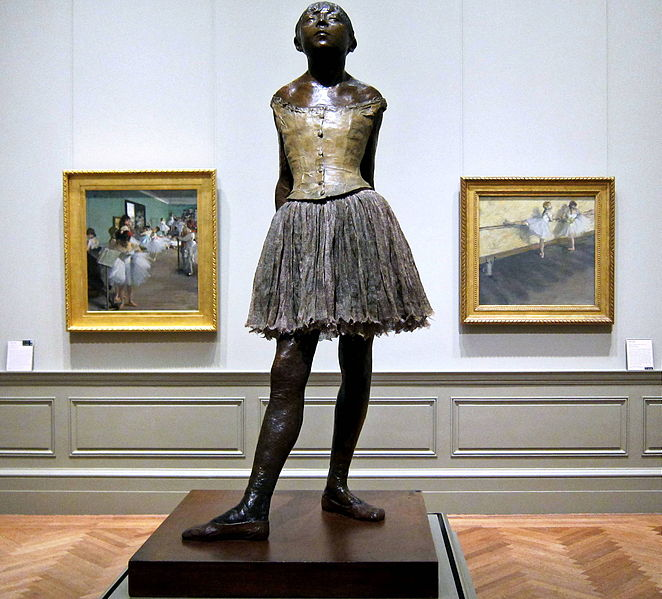 Little Dancer of Fourteen Years, Edgar Degas, bronze, partially tinted, with cotton skirt and satin hair ribbon; wood base. Edgar Degas [Public domain or CC BY-SA 4.0 (http://creativecommons.org/licenses/by-sa/4.0)], via Wikimedia Commons